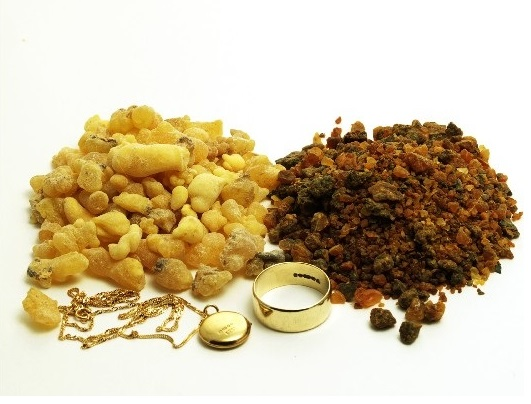 Piles of frankincense and myrrh with gold jewellery isolated on white
